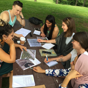 © 2018 Natalie Secen Group looking at maps on a picnic table