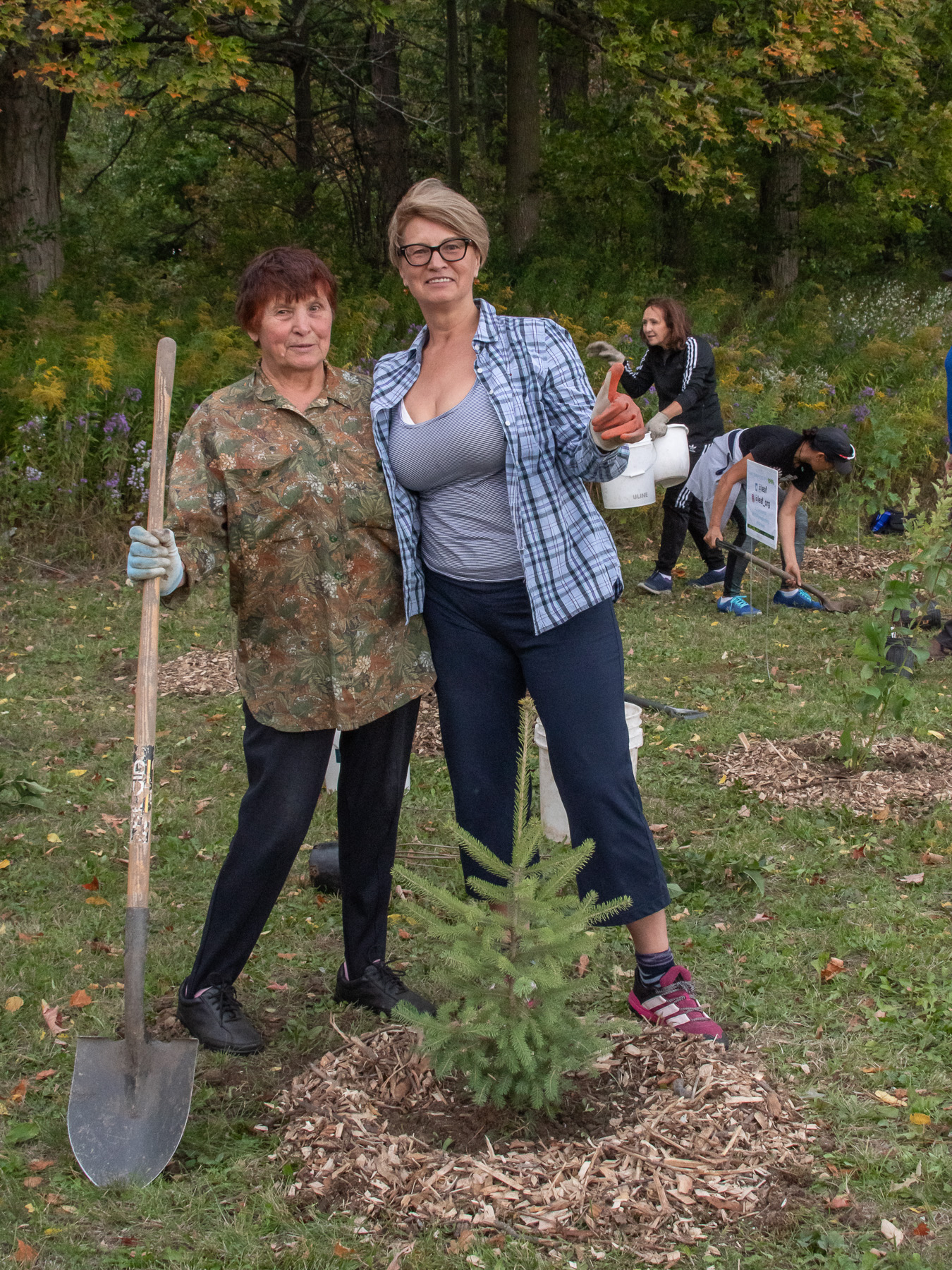 Two women posing next to the tree they planted