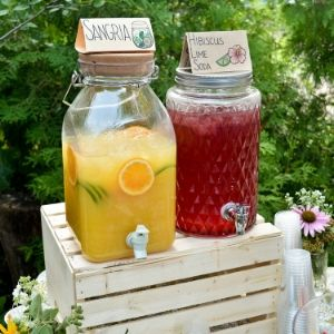 Two jugs on a rustic table display, one serving sangria and the other hibiscus lime soda