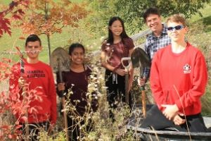 Ben with students standing by new trees and shrubs