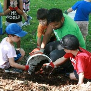 LEAF staff scooping mulch with kids