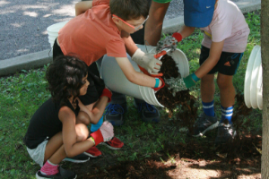 kids pouring out a bucket of mulch
