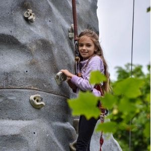 Young girl climbing on the rock wall