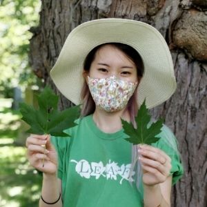 Woman wearing a face mask holds up two maple leaves