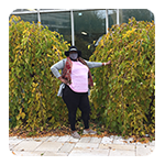 Female TCH tenant standing by tall shrubs