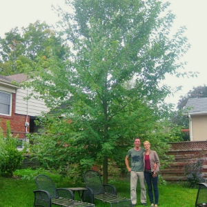 Happy homeowners next to their mature, healthy LEAF tree