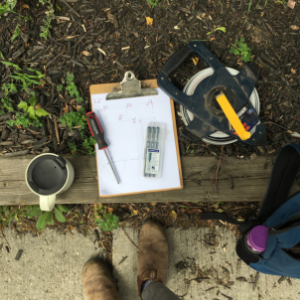 Birdseye view photo of landscape architecture tools. Includes a measuring tape and a sighting map with pens and pencils.