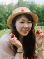 Ruiqi sitting in a park holding fruit