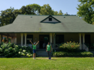 Two junior urban forest rangers posing in front of a house