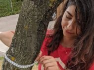 Young woman measuring the width of a tree trunk with measuring tape
