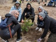 Friends planting a tree together at a LEAF community tree planting event