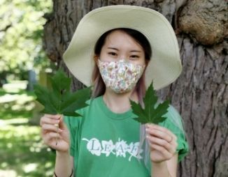 Woman wearing a face masks holds up two maple leaves