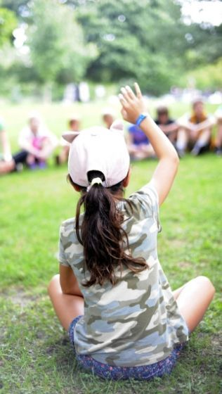 Child sitting in a circle raises her hand