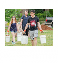 Three people carrying buckets full of mulch