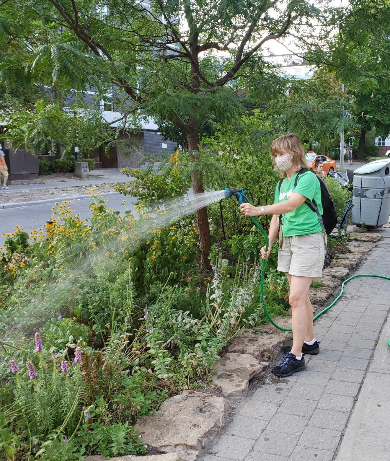 young woman watering a street-side garden