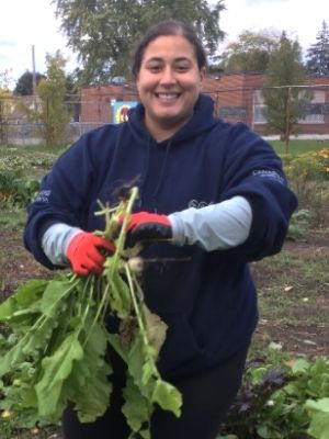 Maiesha holding vegetables in a garden.